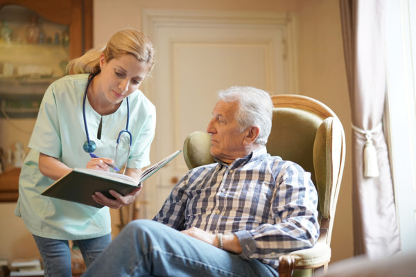 Nurse checking senior male patient results